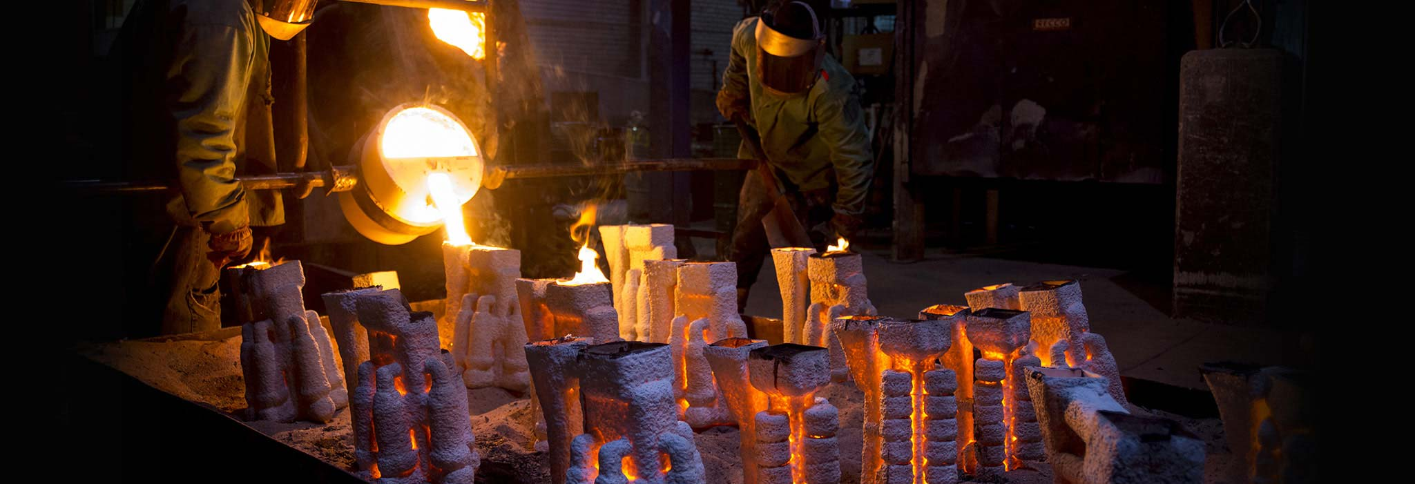 workers pouring molten alloy into ceramic molds for investment cast parts